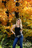 Beautiful teen country girl among fall foliage. Beautiful young teen girl in black tanktop and jeans in front of fall foliage - smiling hands on hips royalty free stock photos