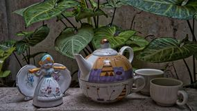 Beautiful teapot and handmade cups. Beautiful teen cups with green plants background rustic and beautiful environment stock images