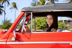 Beautiful teen driving old car and smiling. Beautiful young woman driving old car and smiling Royalty Free Stock Photography