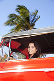 Beautiful teen driving old car and smiling Stock Photography