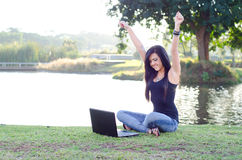 Beautiful teen enjoying technology. Young teen girl with hands up and big smile looking at her laptop Royalty Free Stock Photos