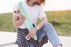 Beautiful teen female skater sitting on ramp at the skate park. Concept of summer urban activities.  royalty free stock image
