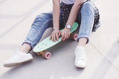 Beautiful teen female skater sitting on ramp at the skate park. Concept of summer urban activities.  stock photography