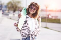Beautiful teen female skater sitting on ramp at the skate park. Concept of summer urban activities.  stock photos