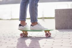 Beautiful teen female skater sitting on ramp at the skate park. Concept of summer urban activities. Closeup legs of Beautiful teen female skater sitting on ramp royalty free stock photos