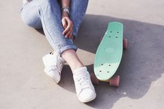 Beautiful teen female skater sitting on ramp at the skate park. Concept of summer urban activities. Closeup legs of Beautiful teen female skater sitting on ramp stock images