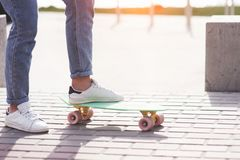 Beautiful teen female skater sitting on ramp at the skate park. Concept of summer urban activities. Closeup legs of Beautiful teen female skater sitting on ramp royalty free stock image