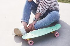 Beautiful teen female skater sitting on ramp at the skate park. Concept of summer urban activities. Closeup legs of Beautiful teen female skater sitting on ramp royalty free stock images