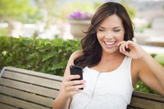 Beautiful Teen Female Texting on Cell Phone Outdoors. Attractive Smiling Young Adult Female Texting on Cell Phone Outdoors on a Bench Stock Photography