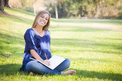 Beautiful Teen Female Writing in a Book Outdoors Royalty Free Stock Images