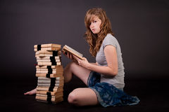 Beautiful teen girl. With books on dark background Stock Photography
