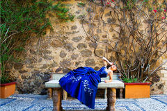 Beautiful teen girl. With an amazing blue dress, laying in a table stone Royalty Free Stock Photo