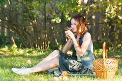 Beautiful teen girl with a basket in a garden smelling a flower Royalty Free Stock Photo