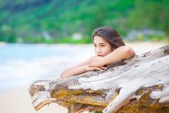 Beautiful teen girl on beach praying by driftwood log. Beautiful biracial asian Caucasian teen girl on secluded  beach praying by driftwood log in sunny Hawaiian Royalty Free Stock Photo