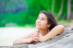 Beautiful teen girl on beach praying by driftwood log. Beautiful biracial  teen girl on tropical  beach praying by driftwood log Royalty Free Stock Photo