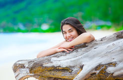 Beautiful teen girl on beach relaxing by driftwood log Stock Image