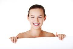 Beautiful teen girl behind big blank billboard Stock Image