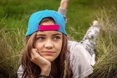 Beautiful teen girl with big eyes in a baseball cap lies on the grass and looks away royalty free stock image