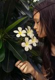 Beautiful teen girl in black tank top with plumeria tree. Boho style portrait. Royalty Free Stock Images