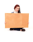 Beautiful teen girl with a blank corkboard Royalty Free Stock Images