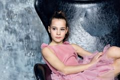 Beautiful teen girl with dark hair in a pink dress sitting royalty free stock image