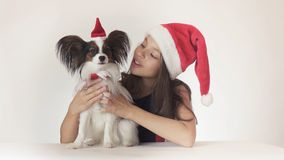 Beautiful teen girl and dog Continental Toy Spaniel Papillon in Santa Claus caps joyfully hugging on white background Royalty Free Stock Photo