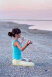 Beautiful teen girl doing yoga exercise lotus pose on the background of the sea at sunset, Stock Photo