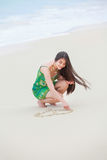 Beautiful teen girl drawing heart in sand on tropical beach Royalty Free Stock Image