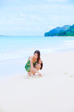 Beautiful teen girl drawing heart in sand on tropical beach Stock Photography