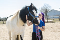 Beautiful teen girl on the farm with her horse. Stock Images