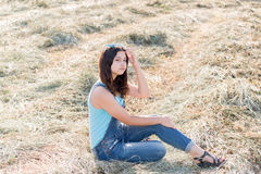 Beautiful teen girl in field with straw Stock Image