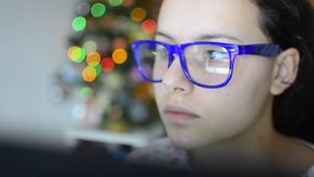 Beautiful teen girl with glasses on touch screen organizer (HD) - Stock Video. Tablet screen is reflected on glasses stock video footage