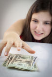 Beautiful teen girl grabs US dollars Royalty Free Stock Image
