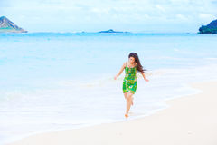 Beautiful teen girl in green dress running along Hawaiian beach Stock Images