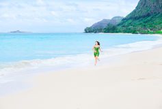 Beautiful teen girl in green dress running on Hawaiian beach Royalty Free Stock Photo