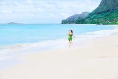 Beautiful teen girl in green dress running on Hawaiian beach Royalty Free Stock Photo