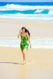 Beautiful teen girl in green dress walking along Hawaiian beach Stock Images