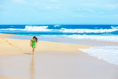 Beautiful teen girl in green dress walking along Hawaiian beach Stock Photos