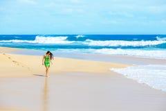Beautiful teen girl in green dress walking along Hawaiian beach Stock Photos
