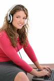 Beautiful Teen Girl with Headphones and Laptop. Beautiful Teen girl sitting on desk wearing headphones working on laptop. Shot in studio over white Stock Images