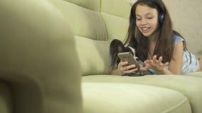 Beautiful teen girl in headphones singing karaoke songs in smartphone with dog Royalty Free Stock Photography