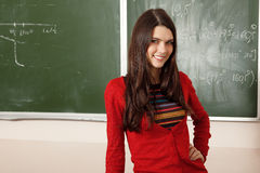 Beautiful teen girl high achiever in classroom near desk Stock Image