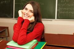 Beautiful teen girl high achiever in classroom over desk happy s Royalty Free Stock Images