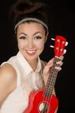 Beautiful teen girl holding a red ukulele smiling Stock Photo