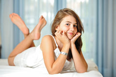 Beautiful teen girl at home  in white dress. Portrait of smiling beautiful teen girl at home in white dress and relaxing on comfortable bed. Luxury interior Royalty Free Stock Photography