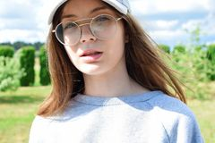 Beautiful teen girl with long brown hair. Portrait of beautiful teen girl with long brown hair, grey cap and stylish glasses looking at camera outdoors on green Royalty Free Stock Photos
