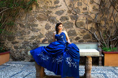 Beautiful teen girl. Lovely teen girl with a blue dress siting in a stone table Stock Photo