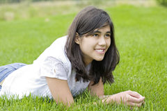 Beautiful teen girl lying on grass Stock Images