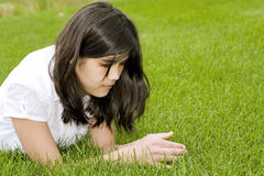 Beautiful teen girl lying on grass Royalty Free Stock Image