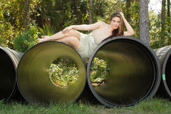 Beautiful Teen Girl Lying on a Large Pipe Royalty Free Stock Photography